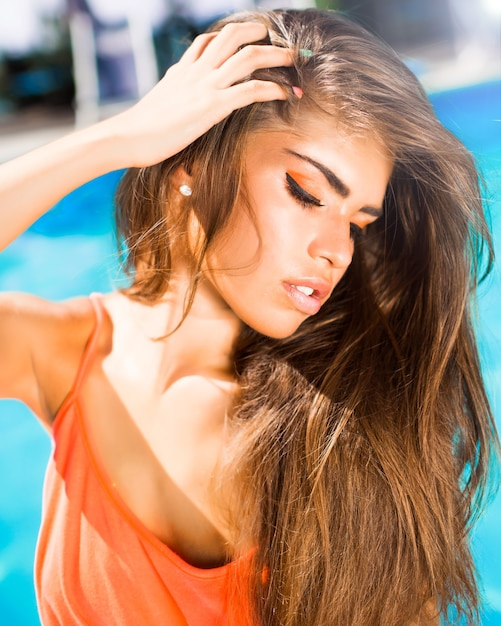 長い黒髪と猫の目、ネオンメイクのアイシャドウと笑顔で日焼けした肌の赤い唇と良い形でプールで女の子の美しさブルネットの肖像画 無料写真