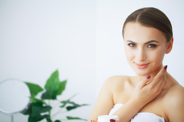 Beauty and care. happy smiling young woman holds cream for face. girl after shower. morning face care. pure skin. Premium Photo