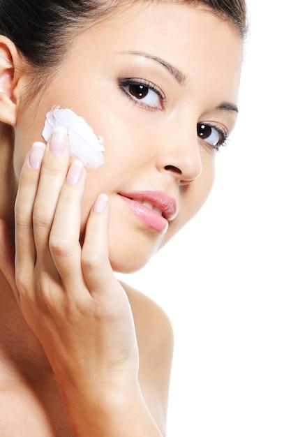 그녀의 뺨에 화장품 보습 크림을 적용하여 그녀의 얼굴의 아름다움 백인 여성 스킨 케어 무료 사진