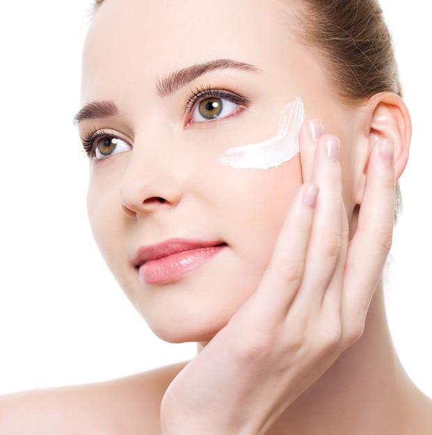 目の下に化粧品を適用する美容白人若い女性 無料写真