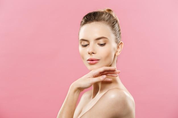Концепция красоты - красивая женщина кавказа с чистой кожей, естественный макияж, изолированных на ярко-розовый фон с копией пространства. Бесплатные Фотографии