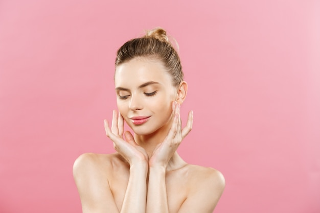Beauty Concept - Beautiful Woman with Clean Fresh Skin close up on pink studio. Skin care face. Cosmetology. Free Photo