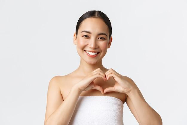 美容、美容、スパサロンのコンセプトです。心のジェスチャーを示すタオルでカリスマ的な笑みを浮かべてアジアの女性は満足、マッサージ療法、白い壁の後に満足している美容クリニックをお勧めします。 Premium写真