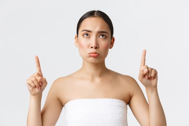 美容、美容、スパサロンのコンセプトです。白いタオルで不機嫌そうな悲しそうなアジアの女の子が不機嫌そうに見て、指を上に向けてがっかりし、美容院やマッサージ療法で不平を言っています。 Premium写真