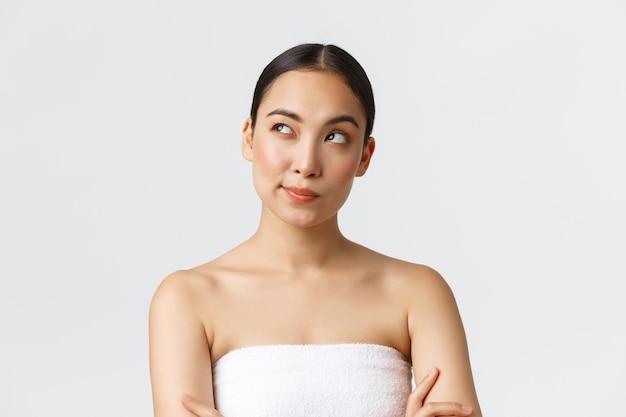 美容、美容、スパサロンのコンセプトです。左上隅を見て、考えて、意思決定、白い壁に立ってバスタオルで思いやりのある創造的なアジアの女性。 Premium写真