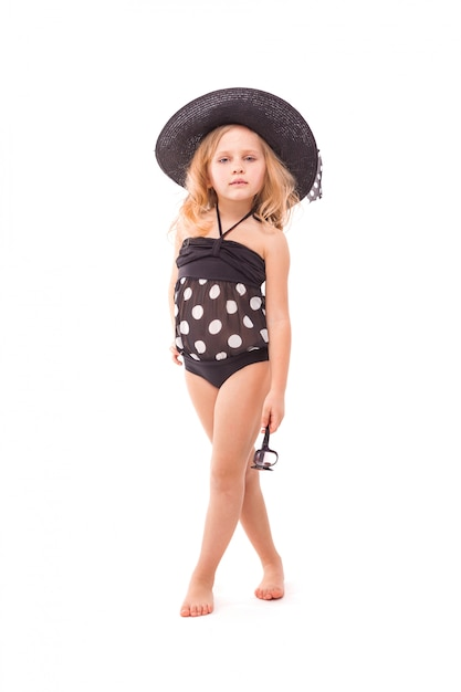Beauty cute little girl in in black swimwear and black hat hold glasses Premium Photo