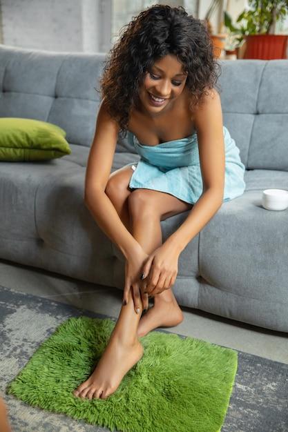 뷰티 데이. 집에서 그녀의 일상적인 스킨 케어 루틴을 하 고 수건에 아프리카 계 미국인 여자. 소파에 앉아 마사지하고 다리 피부에 보습제를 바르십시오. 무료 사진