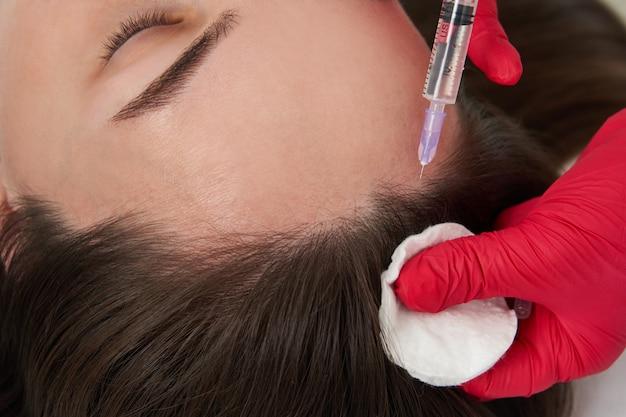 Врач красоты делает инъекции красоты омоложения гиалуроновой кислоты в голову красивой молодой женщины Premium Фотографии