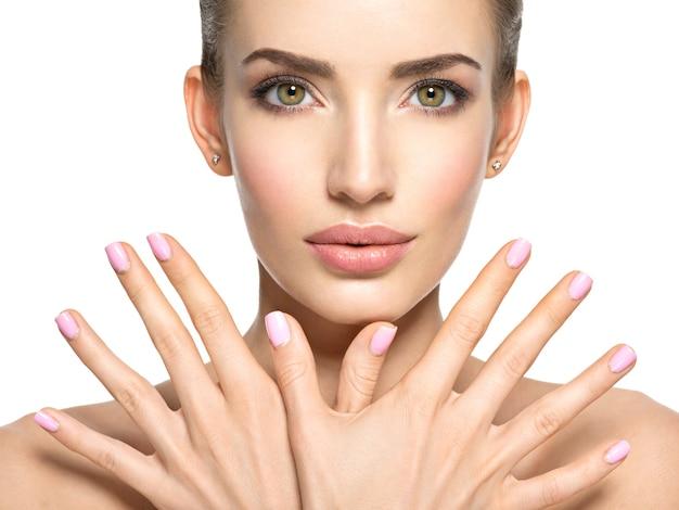 若い美しい女性の美しさの顔-白で隔離。素敵な指の爪を持つ女性。かなり若い女の子はピンクの爪で顔の前に手を示しています 無料写真