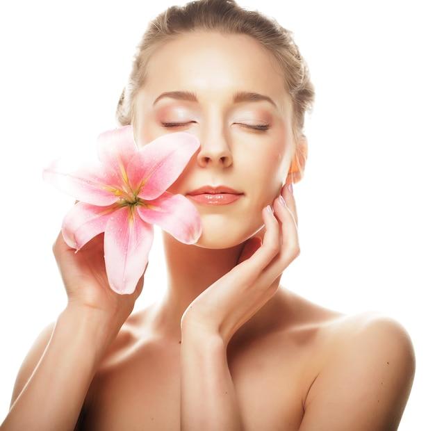 白で隔離されるピンクのユリを持つ若い女性の美しさの顔 Premium写真