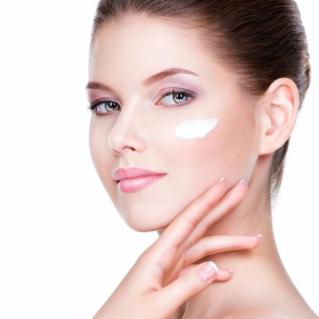 뺨에 화장품 크림을 가진 젊은 여자의 아름다움 얼굴. 스킨 케어 개념. 근접 촬영 초상화 흰색 절연입니다. 무료 사진