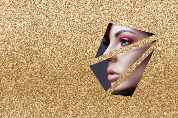 Beauty face red eye makeup of a young girl in a slit hole of yellow gold paper. woman with beautiful