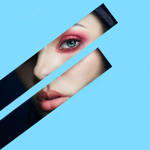 Beauty face red makeup eyes of a young woman in a slit hole of blue paper. woman with beautiful make