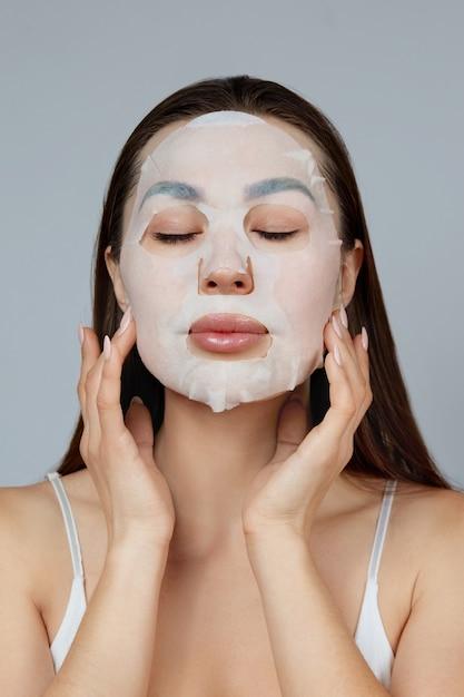 뷰티 페이스 스킨 케어. 아름 다운 여자는 얼굴에 천으로 보습 마스크를 적용합니다. 화장품 마스크와 여자 모델입니다. 페이셜 트리트먼트 프리미엄 사진