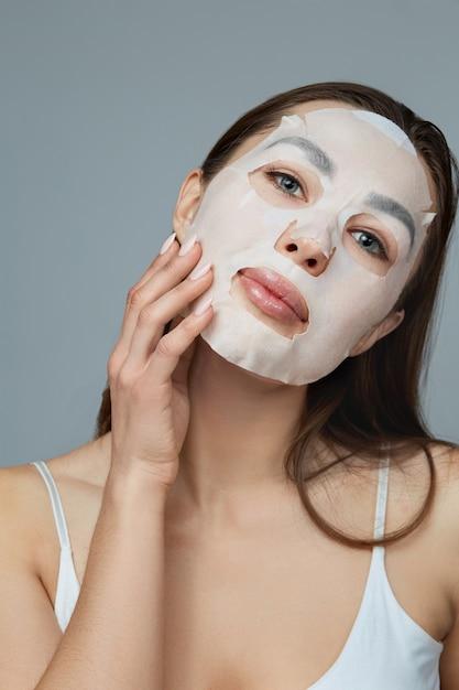 뷰티 페이스 스킨 케어. 여자는 얼굴에 천 보습 마스크를 적용합니다. 화장품 마스크와 여자 모델입니다. 페이셜 트리트먼트 프리미엄 사진
