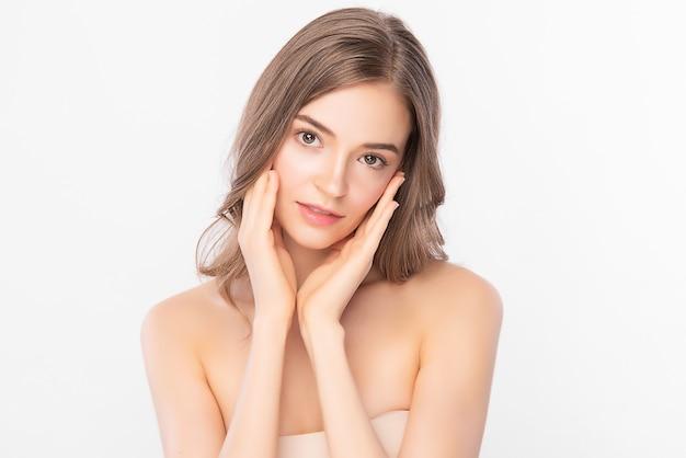 Красота лица. улыбаясь азиатской женщины касаясь здоровой кожи портрета. красивая счастливая девушка-модель со свежей сияющей увлажненной кожей лица и естественным макияжем Premium Фотографии