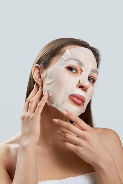 뷰티 페이셜 마스크. 얼굴에 천 보습 마스크와 아름 다운 젊은 여자. 피부 관리 프리미엄 사진