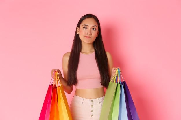 Концепция красоты, моды и образа жизни. портрет нерешительной симпатичной азиатской девушки с хозяйственными сумками, надутой, делая выбор, решая купить или нет, глядя в левый верхний угол. Premium Фотографии