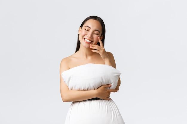 Красота, мода и концепция социальных сетей. великолепная женщина-блогерша женственного образа жизни, одетая в подушку, как платье, прикреплена к телу ремнем вокруг отходов, смеется и радостно улыбается Premium Фотографии