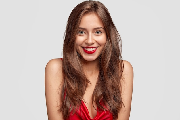 Beauty, fashion, makeup and people concept. lovely happy woman with red lipstick, shows white perfect teeth, has healthy skin, long dark hair, isolated over white wall, expresses happiness Free Photo