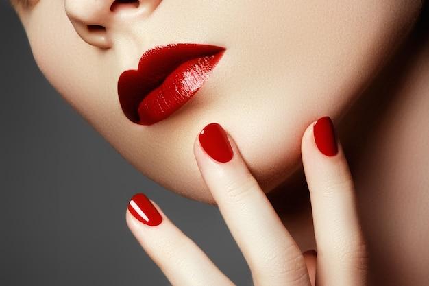 美容ファッションモデルの顔。赤い爪で手入れの行き届いた手 Premium写真