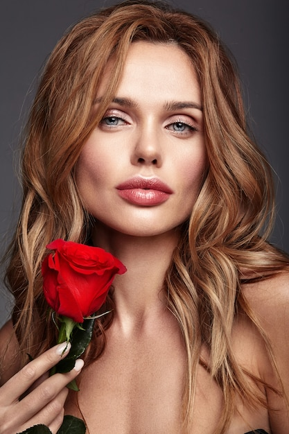 Beauty fashion portrait of young blond woman model with natural makeup and perfect skin with beautiful rose  posing Free Photo