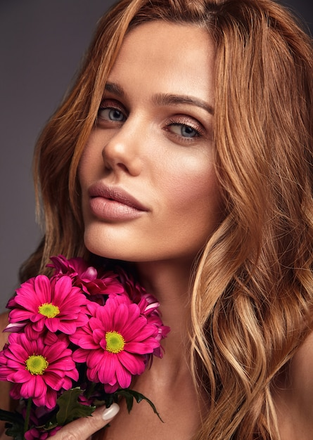 Beauty fashion portrait of young blond woman model with natural makeup and perfect skin with bright сrimson chrysanthemum flower posing Free Photo