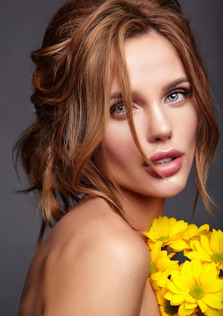 Beauty fashion portrait of young blond woman model with natural makeup and perfect skin with bright yellow chrysanthemum flower posing Free Photo
