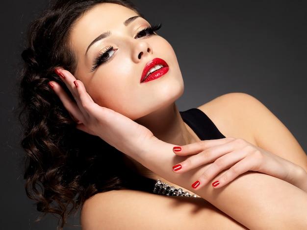 Donna di modo di bellezza con unghie rosse, labbra e trucco occhi d'oro Foto Gratuite
