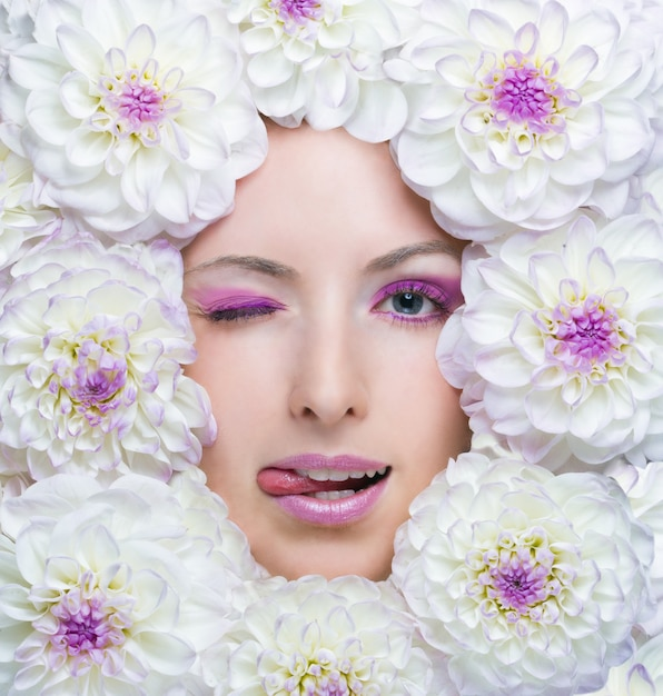 Beauty girl with white flowers around her face. dahlia flowers. Premium Photo