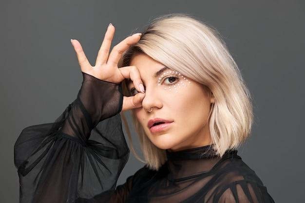 아름다움, 매력, 럭셔리 및 패션 개념. 플레어가 격리 된 포즈, 확인 표시에 엄지 손가락과 검지 손가락을 연결하는 세련된 투명 검은 색 블라우스에 매력적인 멋진 젊은 여성의 프로필 샷 무료 사진