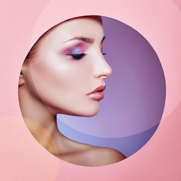 Beauty makeup cosmetics nature fashion woman in a round hole circle in pink paper, copy space advert