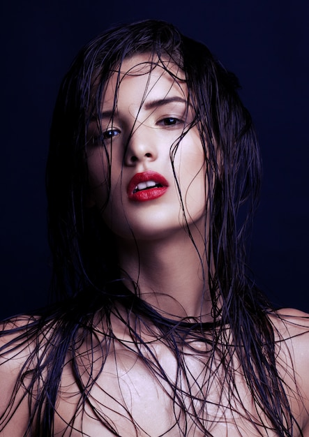 Beauty makeup wet hair fashion model with red lips on black wall Premium Photo
