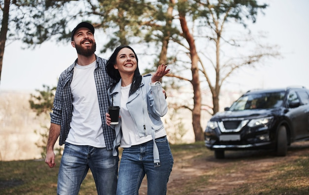 Beauty of the nature. couple have arrived to the forest on their brand new black car Premium Photo