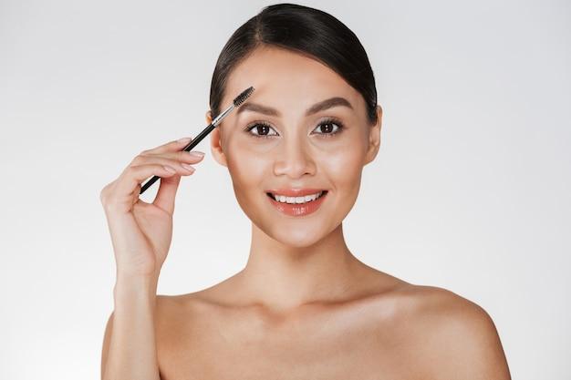 Картина красоты милой молодой женщины с волосами в плюшке смотря на камере и расчесывая ее брови с щеткой, изолированная над белизной Бесплатные Фотографии