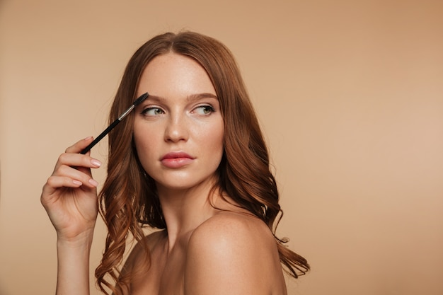 Beauty portrait of calm ginger woman with long hair looking away and posing sideways while combing her eyebrows with brush Free Photo