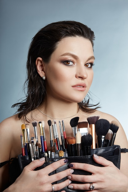 Beauty portrait of a female makeup artist. makeup brushes in the hands of a girl Premium Photo