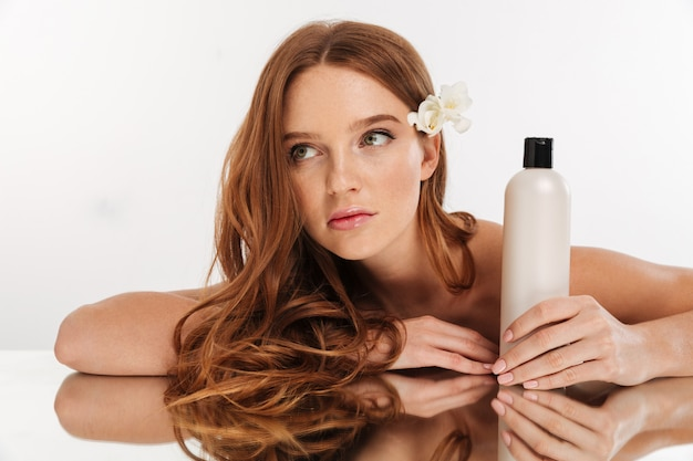 Beauty portrait of ginger woman with flower in hair sitting by the mirror table with bottle of lotion while looking away Free Photo