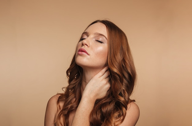Beauty portrait of mystery ginger woman with long hair posing with closed eyes while touching her neck Free Photo