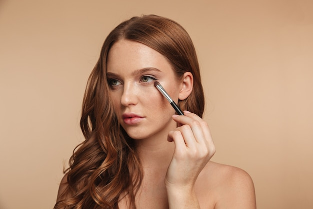 Beauty portrait of mystery smiling ginger woman with long hair looking away while applying cosmetics with brush for eyeshadow Free Photo