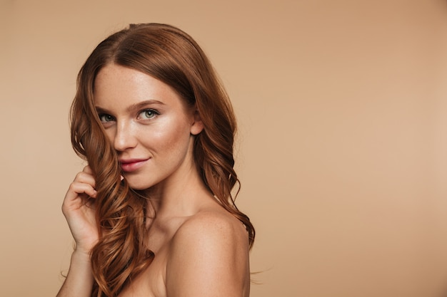 Ritratto di bellezza della donna sorridente dello zenzero di mistero con capelli lunghi che posano lateralmente e che guardano Foto Gratuite