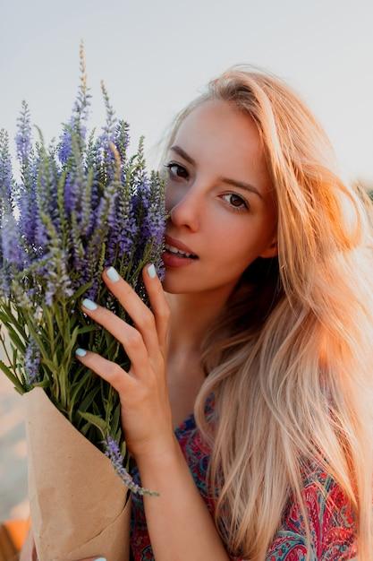 Портрет красоты прекрасной белокурой женщины с букетом лаванды, смотрящей на камеру. идеальная кожа. естественный макияж. Бесплатные Фотографии