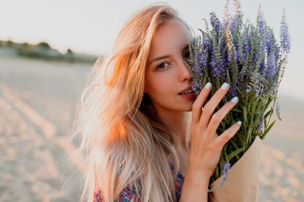 カメラを見ているラベンダーの花束とロマンチックなブロンドの女性の美しさの肖像画。完璧な肌。ナチュラルメイク。 無料写真