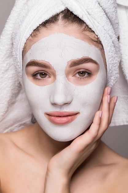 白い栄養マスクまたは顔、白い壁が分離されたクリームで頭の上のタオルで女性の美しさの肖像画。スキンケアクレンジングエコオーガニック化粧品スパリラックスコンセプト 無料写真