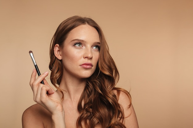 Beauty portrait of pensive ginger woman with long hair looking up while holding cosmetics brush Free Photo