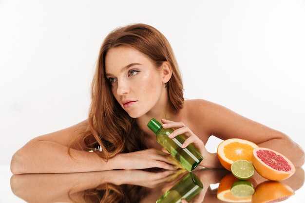 Beauty portrait of pretty ginger woman with long hair reclines on mirror table near the fruits and bottle of lotion Free Photo