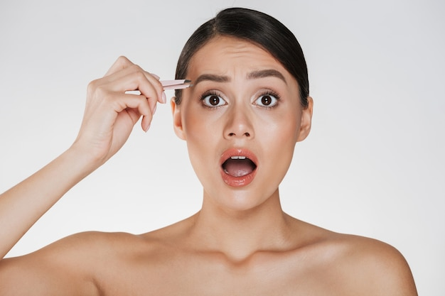 Beauty portrait of pretty half-naked woman with brown hair yelling in pain while plucking eyebrows using tweezers, isolated over white Free Photo