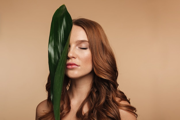 Beauty portrait of sensual ginger woman with long hair posing with green leaf Free Photo
