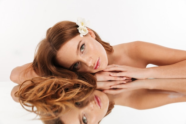 Beauty portrait of smiling ginger woman with flower in hair lying on mirror table while looking Free Photo