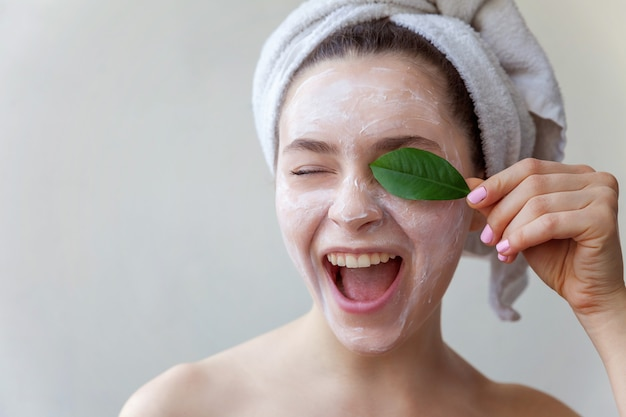 Beauty portrait of woman with white nourishing mask or creme on face and green leaf in hand Premium Photo